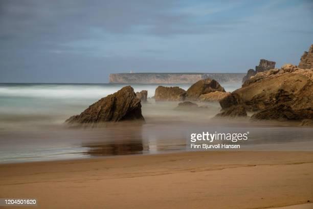 beach of sagres on the algarve coast in portugal - caboo sao vicente in the background - finn bjurvoll stockfoto's en -beelden
