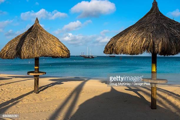 Beach palapas at Palm Beach with sailboats anchored close to shore