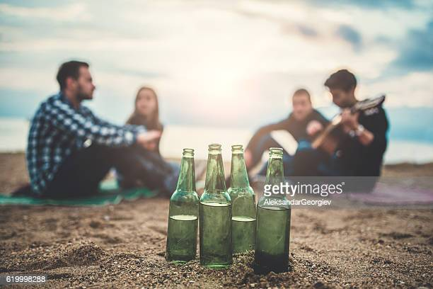 Beach Party with Beer Bottles and Friends with Guitar