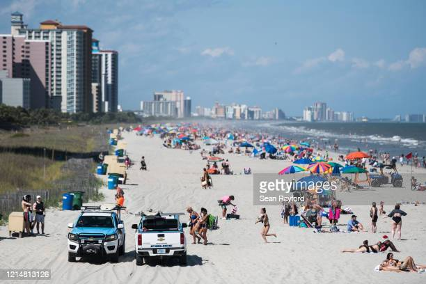 Beach Patrol police officers talk to beach goers from their vehicles May 23 2020 in Myrtle Beach South Carolina Businesses including amusement parks...