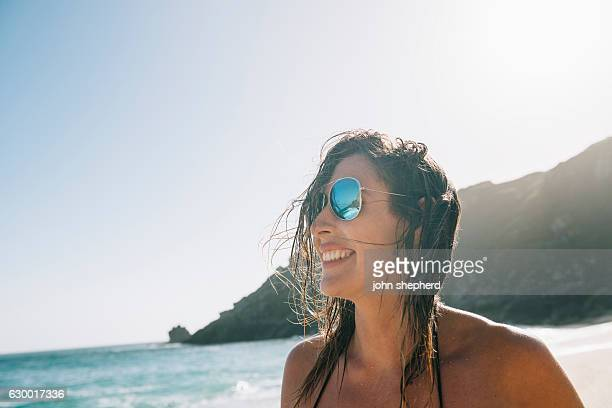 Beach portrait of a young woman, backlit in sunshine.