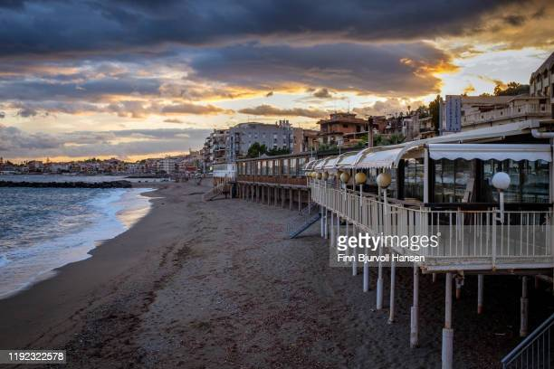 beach restaurant in giardini naxos. sunset and the city in the background - finn bjurvoll stock pictures, royalty-free photos & images