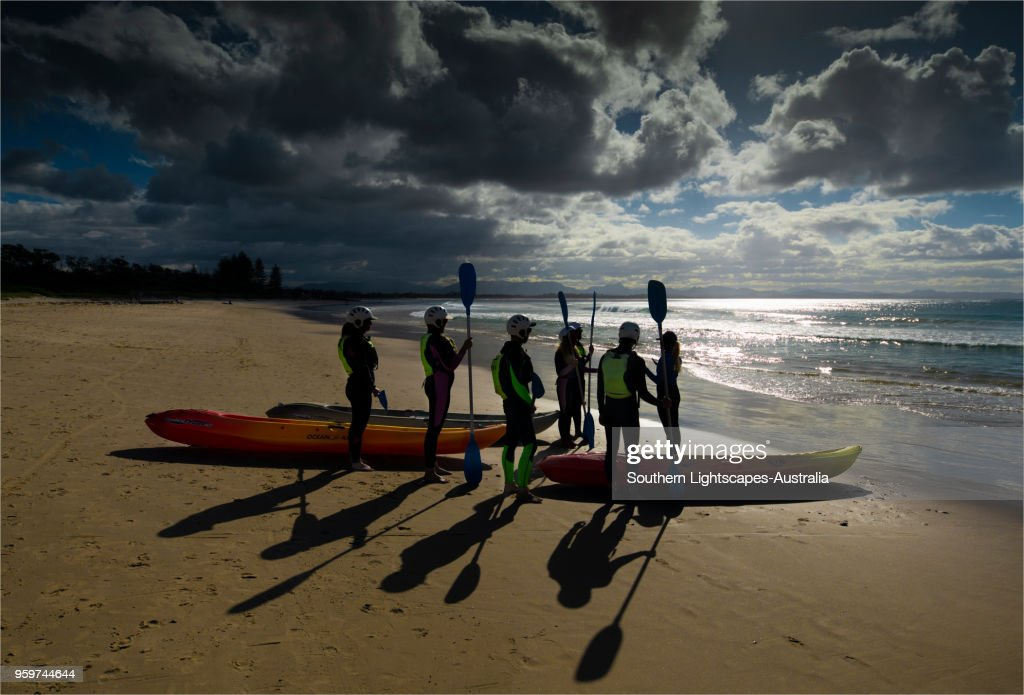 Beach scene and a group of people ready to go sea kayaking, Byron Bay, New south Wales, Australia. : Stock-Foto