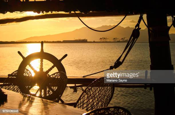 Beach scene in sunset with wooden steering wheel