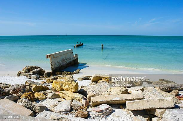 Beach scene showing concrete rubble and the remains of a pier and the beautiful turquoise waters of the Gulf of Mexico in the Sarasota, FL area.