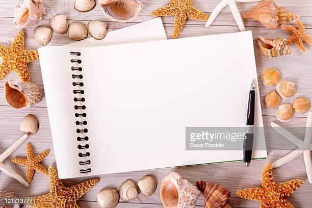 Beach scene with blank writing book