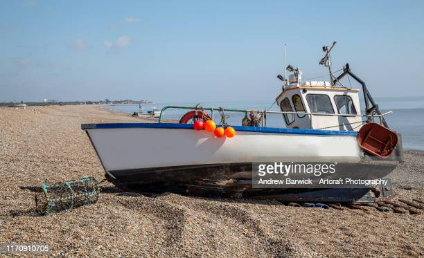 beach scene with boats - fishing industry stock pictures, royalty-free photos & images