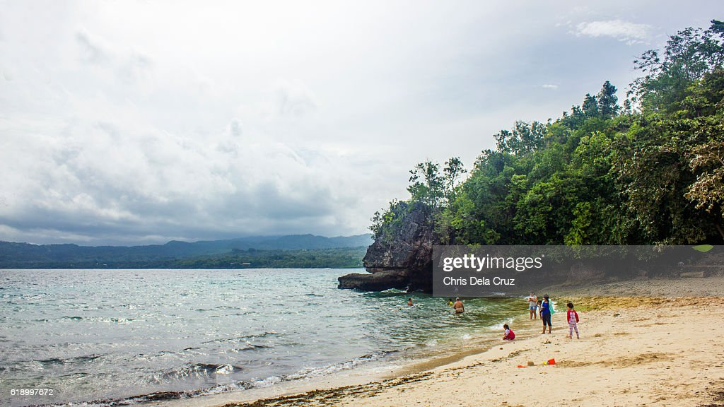 Beach shore with people enjoying the water : Stock Photo