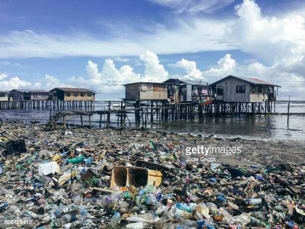 beach surrounding a water village in borneo covered by mounds of garbage - isla de borneo fotografías e imágenes de stock
