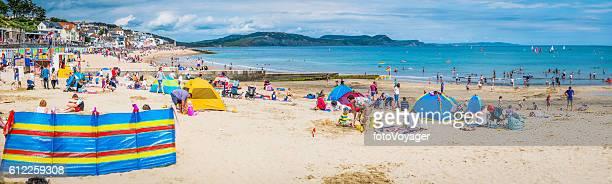 beach tourists sunbathers at seaside holiday resort panorama dorset uk - quebra ventos imagens e fotografias de stock