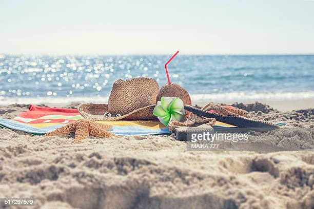 Beach towel, starfish, hat, coconut and flip flops