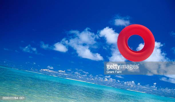 beach toy in air, sea and sky in background - red tube stock pictures, royalty-free photos & images