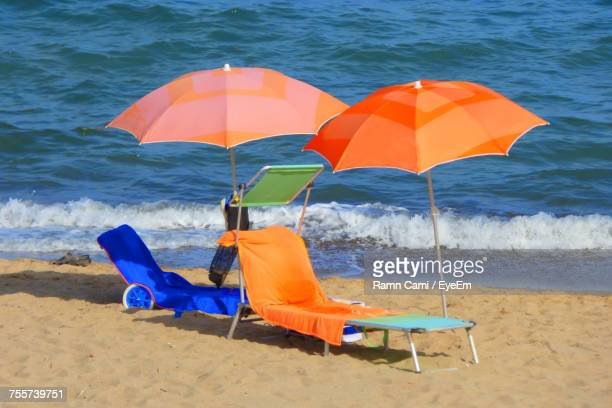Beach Umbrella And Lounge Chairs On Shore At Beach