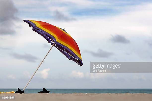 A beach umbrella and sandals are seen on the nearly empty beach on August 19 2009 in Hollywood Florida An estimated 201 million people visited...