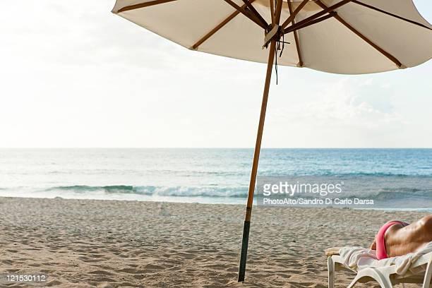 Beach umbrella on beach, semi-naked person lying on deckchair