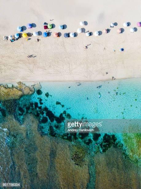 sombrillas de playa y mar azul. escena de la playa desde arriba - lombok fotografías e imágenes de stock