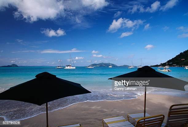 beach umbrellas at cane garden bay on tortola - cane garden bay stock pictures, royalty-free photos & images