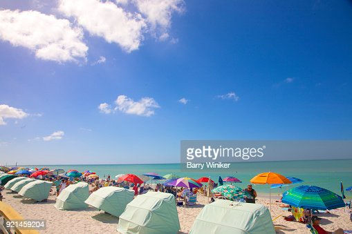 beach umbrellas cabanas blue sky
