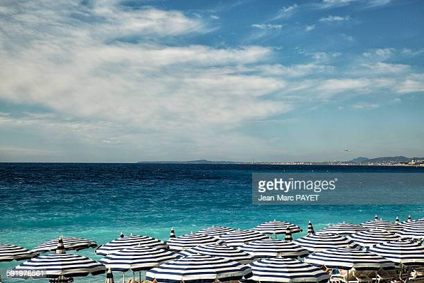 beach umbrellas on beach of the city of nice - jean marc payet stock pictures, royalty-free photos & images