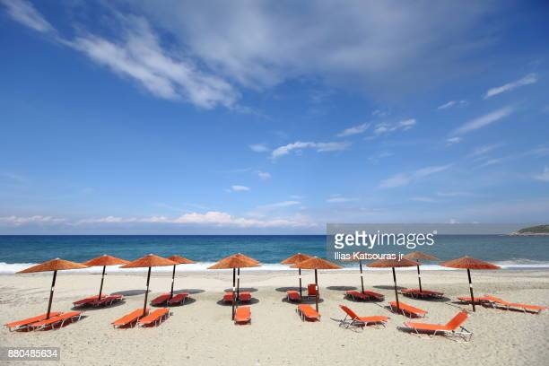 beach umbrellas on empty beach in greece, under blue cloudy sky - thessaly stock pictures, royalty-free photos & images