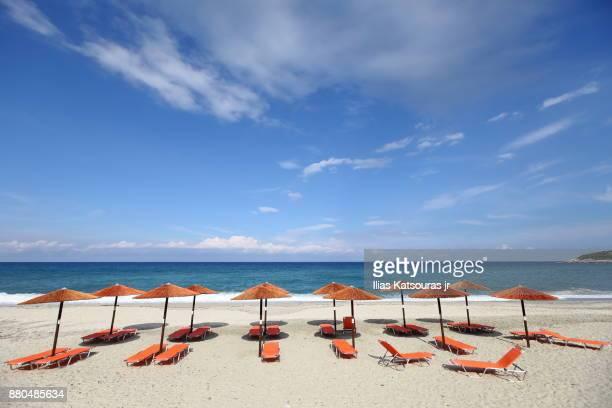 Beach umbrellas on empty beach in Greece, under blue cloudy sky