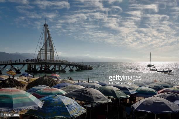 Beach umbrellas on Los Muertos beach at the Pier and Sierra Madre mountains Puerto Vallarta