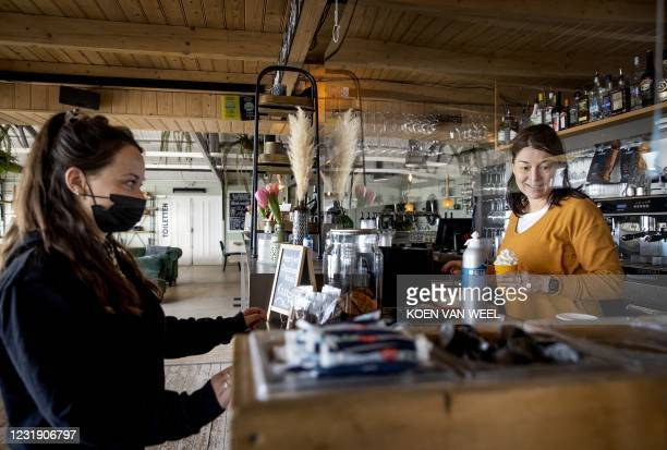 Beach visitor buys drinks from the take away of a beach pavilion in Wijk aan Zee, on March 24 2021. - Due to the Covid-19 pandemic, the catering...