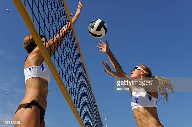 beach volley action in mid-air - beachvolleybal stockfoto's en -beelden