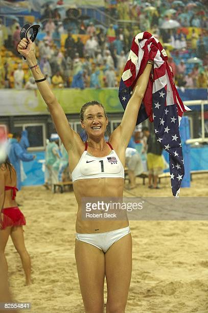 2008 Summer Olympics USA Kerri Walsh victorious with flag after winning Women's Gold Medal Match vs China at Chaoyang Park BV Ground Rain weather...
