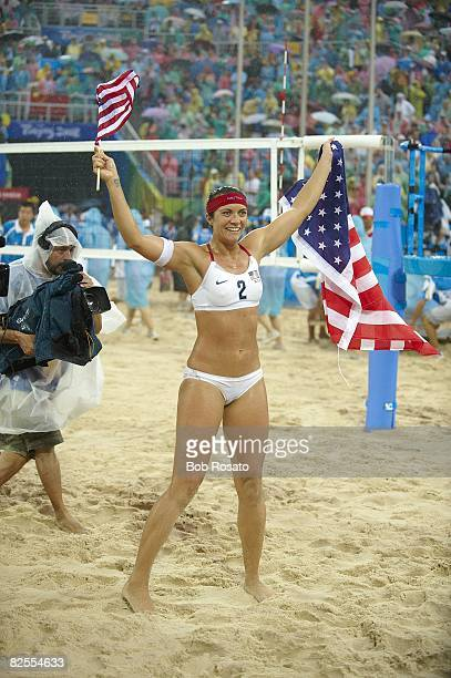 2008 Summer Olympics USA Misty MayTreanor victorious with flag after winning Women's Gold Medal Match vs China at Chaoyang Park BV Ground Rain...