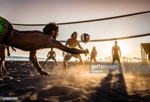 beach-volleyball bei sonnenuntergang! - volleyball mannschaftssport stock-fotos und bilder