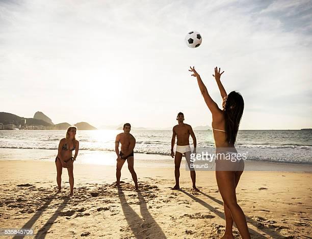 Beach volleyball at sunset.