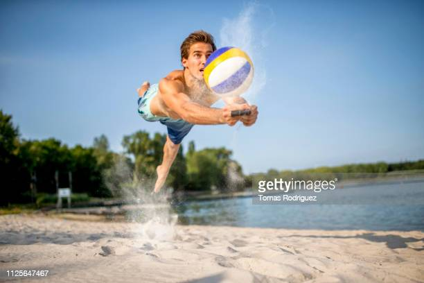 beach volleyball player digging the ball - drive ball sports stock pictures, royalty-free photos & images