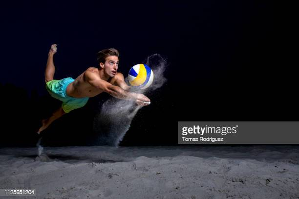 beach volleyball player digging the ball - strand volleyball der männer stock-fotos und bilder