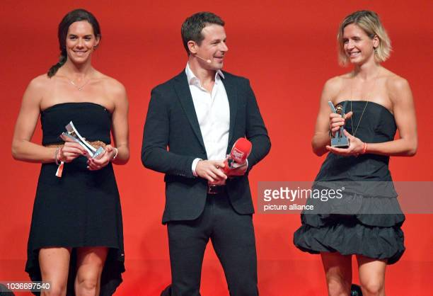 Beach volleyball players Kira Walkenhorst and Laura Ludwig stand on stage together with presenter Alexander Bommes at the Spor BildAward ceremony in...