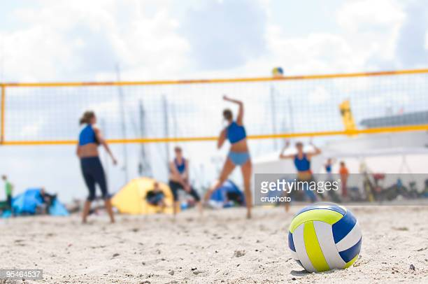 beach volleyball with closeup of ball in foreground - beachvolleybal stockfoto's en -beelden