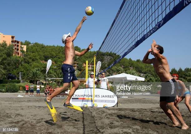 Beach volleyball World Champion Julius Brink throws the ball during a fun beach volleyball match against 6 World Champions and Olympic medalist at...