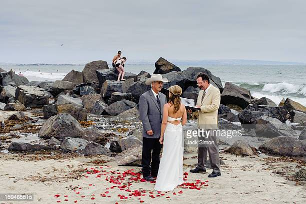Beach wedding while another couple frolics on the rocks. Humor