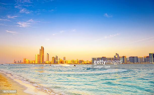 Beach with backdrop of Abu Dhabi skyline at sunset
