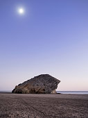 Beach with big rocks and sand illuminated by the full moon to the dusk. Cabo de Gata - Nijar Natural Park, Cala Monsul, Beach, Biosphere Reserve, Almeria,  Andalusia, Spain