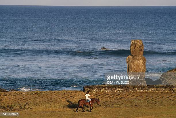 Beach with Moai and woman on horseback Rapa Nui National Park Easter Island Chile Polynesian civilisation