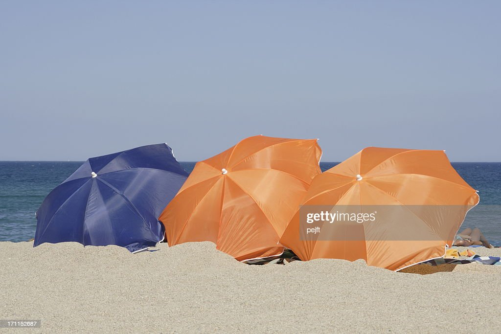 Beach with orange and blue parasols : Stock Photo