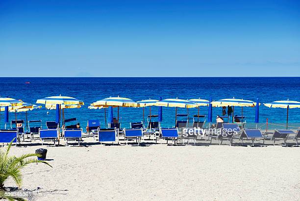 beach with parasols and lounge chairs in scilla,calabria,italy - reggio calabria stock pictures, royalty-free photos & images