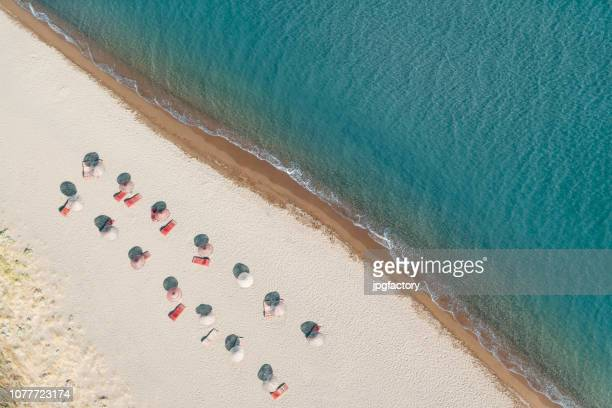 beach with red umbrellas - aegean sea stock pictures, royalty-free photos & images