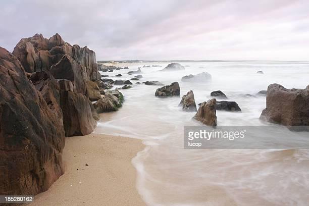 Playa con rocas y borroso olas al atardecer