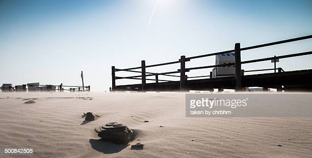 Beach with sand and railing.