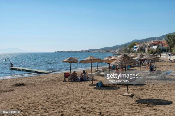 beach with sunshades in north aegean sea on a sunny autumn day,kucukkuyu. - emreturanphoto stock pictures, royalty-free photos & images