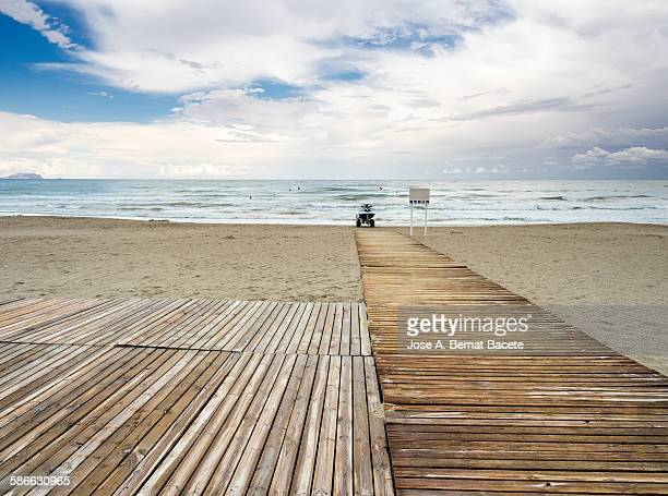 beach with the soil covered with planks of wood - floorboard stock photos and pictures
