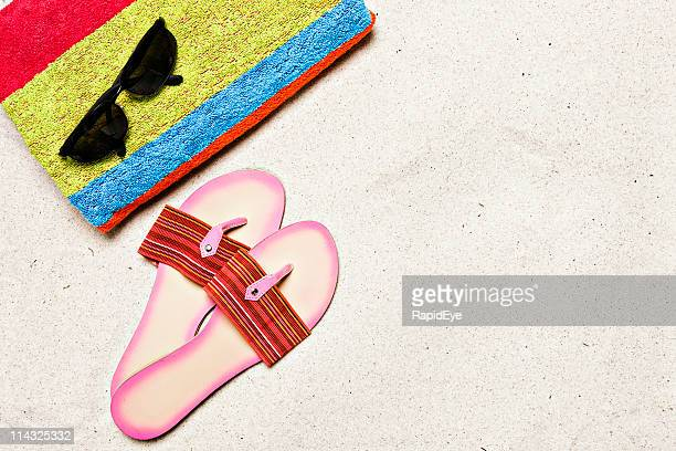 Beach with towel, sunglasses, sandals and copy space