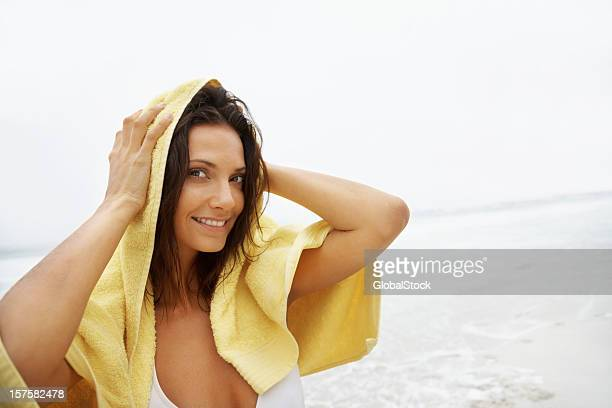 Beach woman wiping her hair with a towel